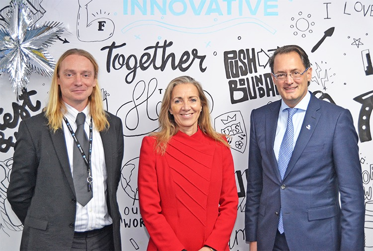 The Floow's CIO, Sam Chapman, and CEO, Aldo Monteforte, with UK Minister for International Trade, Baroness Fairhead in front of The Floow's basement wall