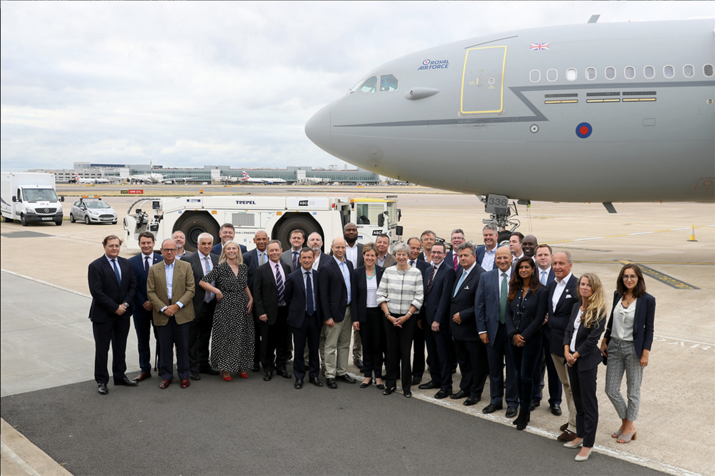 group of people stood next to a plane smiling