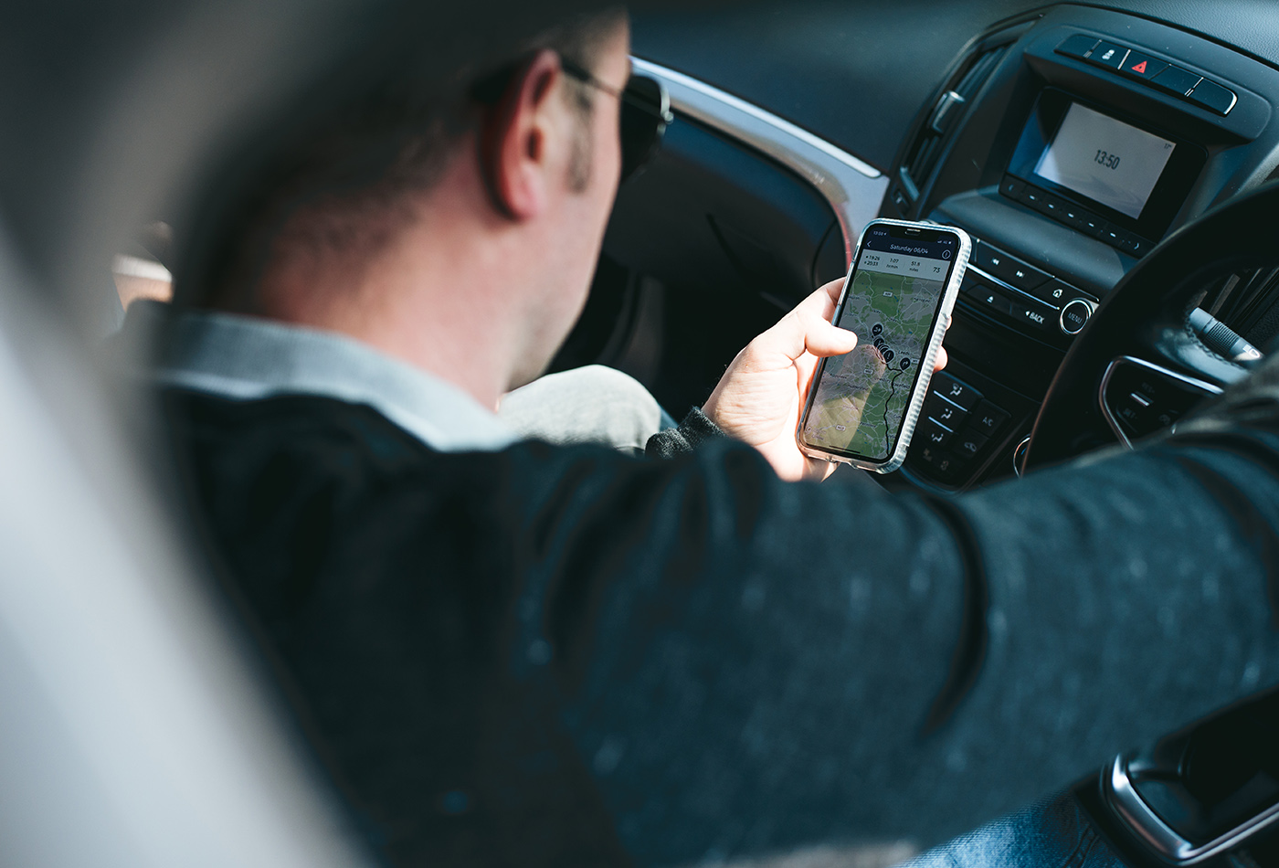man looking at phone when sitting in driver's seat