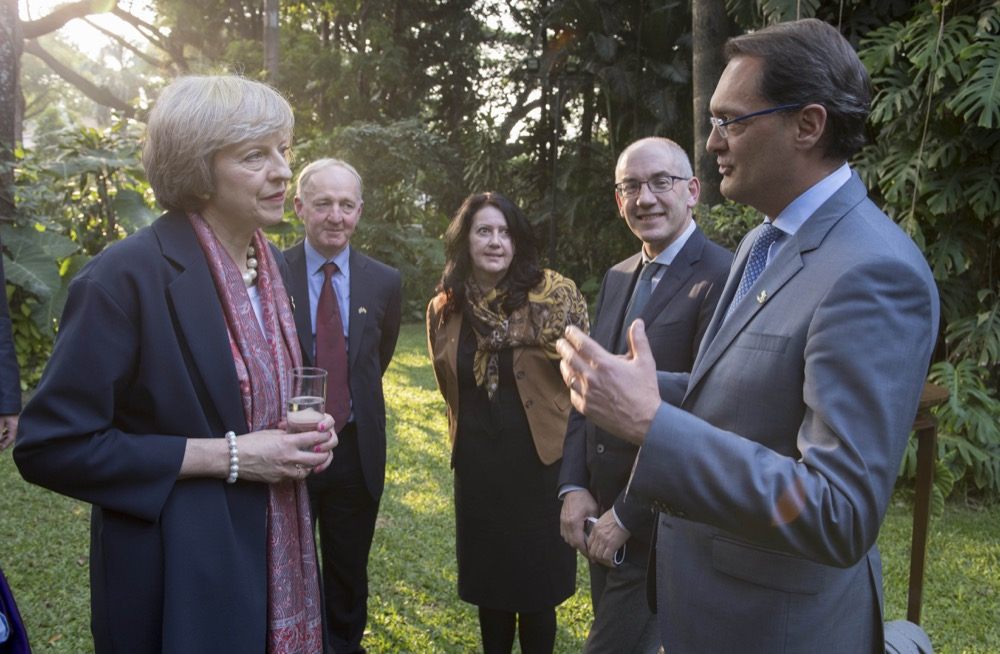 The Floow CEO, Aldo Monteforte, and PM Theresa May talking to each other on trade trip in India with other delegates looking on