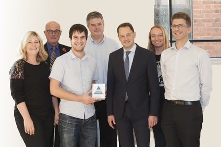 Members of The Floow team holding their Prince Michael award and smiling