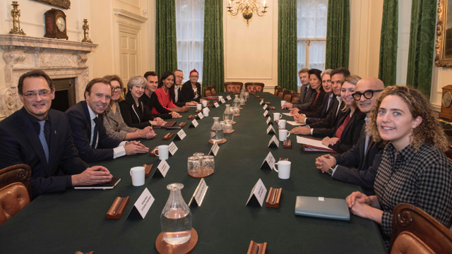 Series of people sat round the cabinet table in No.10 looking at the camera and smiling