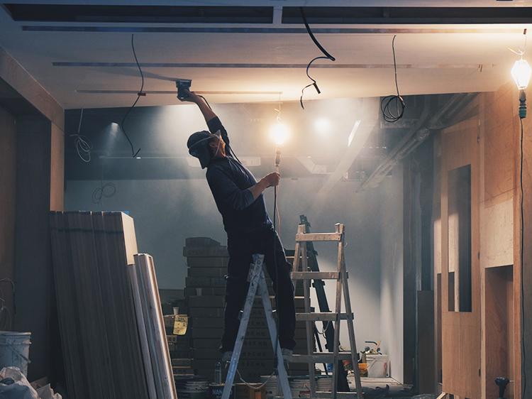 Man on ladder sanding a ceiling