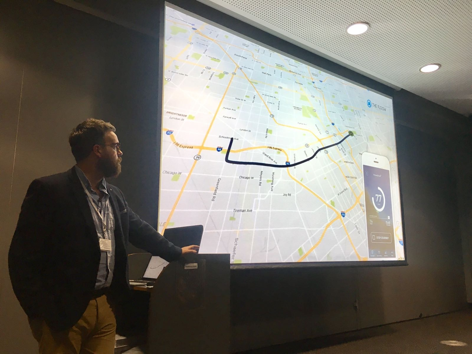 Man leaning against podium whilst presenting on screen which showcases a map